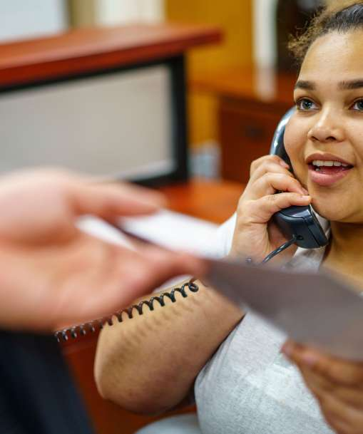 Office administration student handles paperwork and answers the telephone