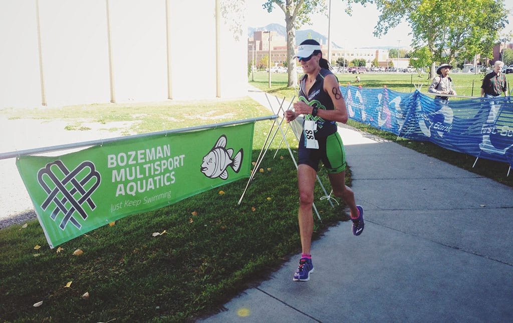 Milica McDowell running in front of a Bozeman Multisport Aquatics banner at the Montana State University Triathlon wearing a Montana Multisport tri kit