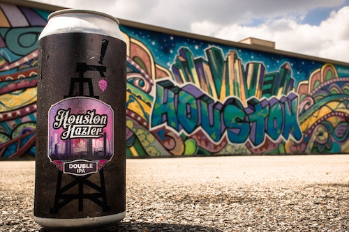 houston hazier ipa craft beer can in front of graffiti by josh olalde
