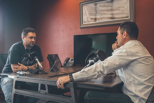 two-men-sitting-recording-a-podcast-for-business