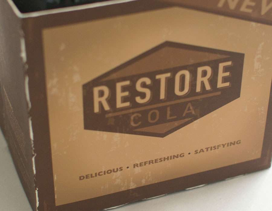 This is a three-quarters view of the Restore Cola Bottle packaging done by Kevin Dench