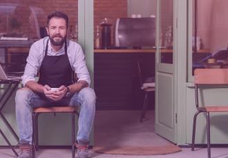 Emprendedor afuera de su cafetería pensando en mejorar su historial de crédito