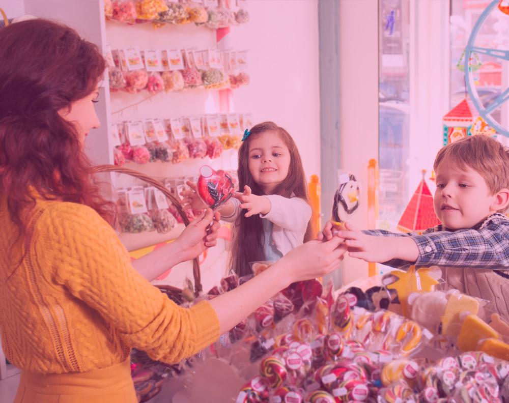 Dueña de negocio entregando dulces a dos niños