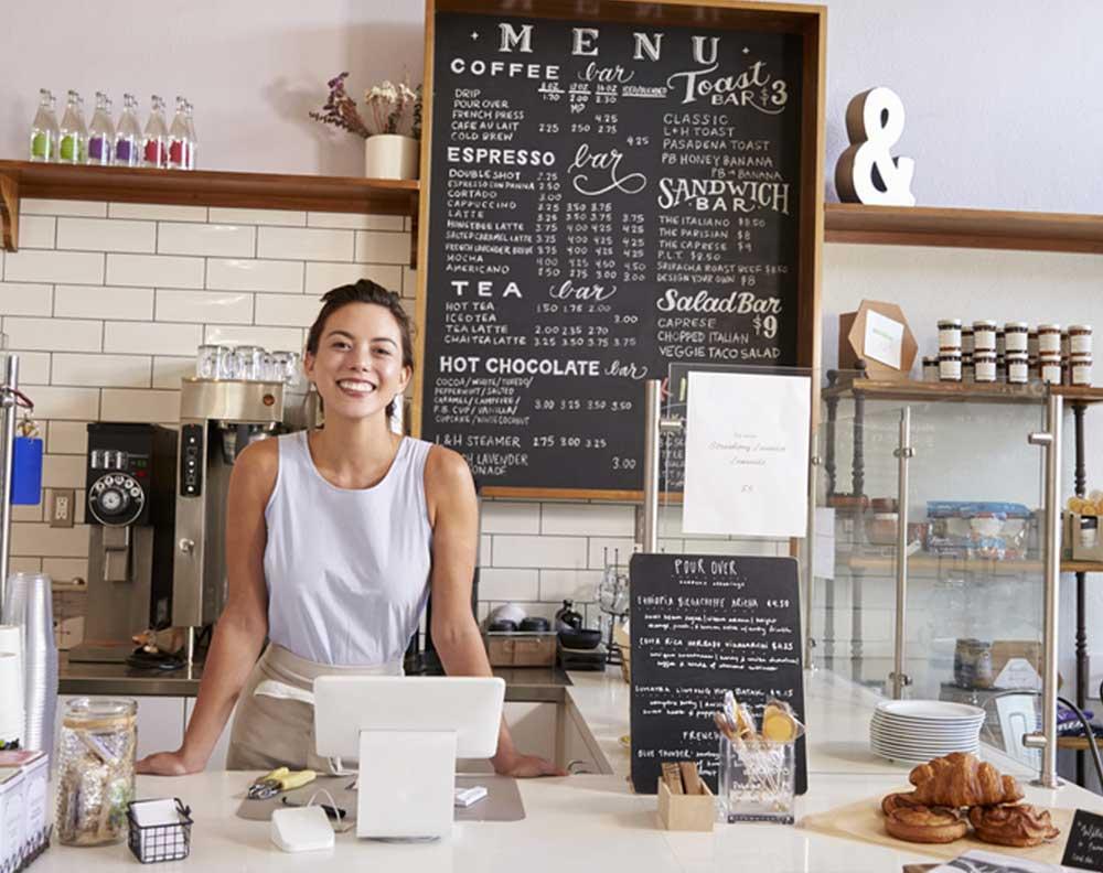 Mujer joven en su negocio utilizando herramientas digitales para administrarlo
