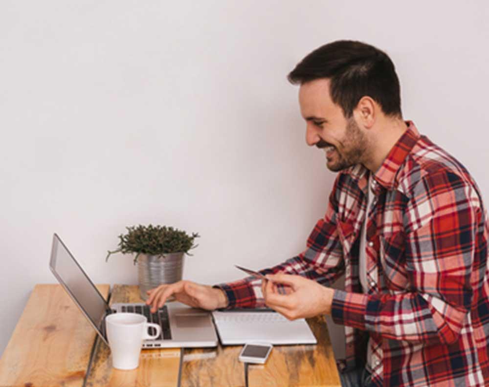 Hombre joven revisando su score crediticio en su computadora para aumentar su linea de crédito