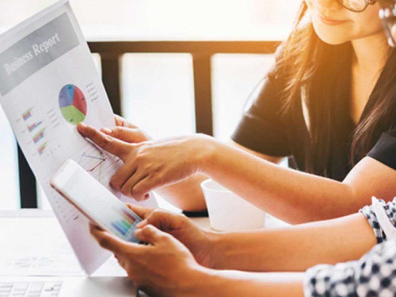 Dos mujeres jóvenes revisando la salud financiera de su negocio con una aplicación móvil