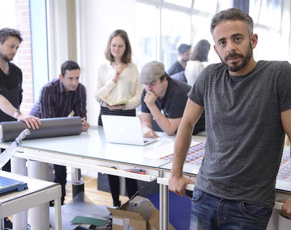 Hombre de 41 años en su pyme con sus socios al fondo trabajando para mejorar la empresa