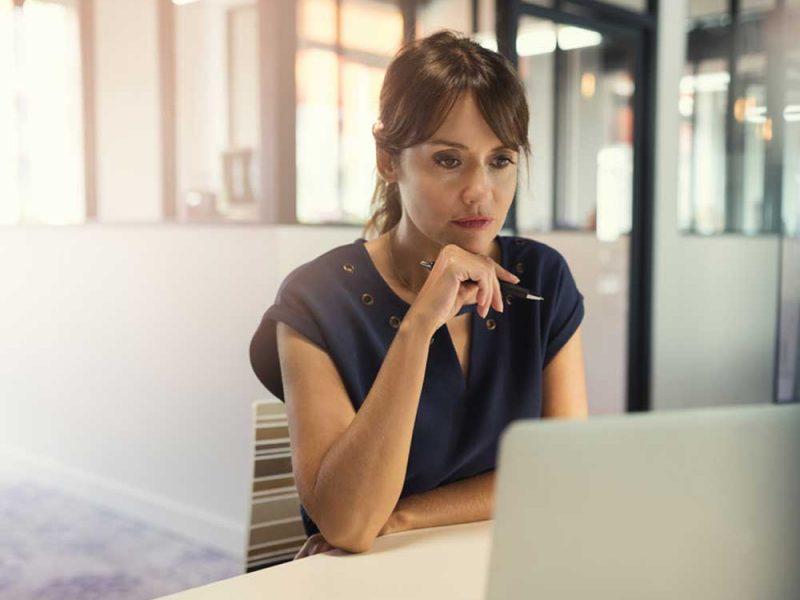 Mujer joven decidiendo entre pedir un crédito a un banco o a una fintech