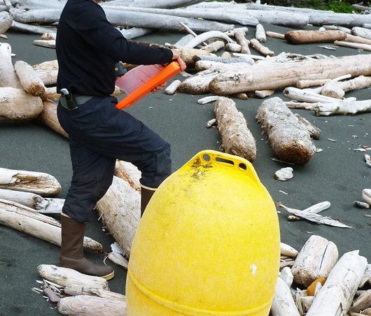 NOAA Marine Debris Program Deputy Director Jason Rolfe examines an unusual, large, yellow buoy found on the south side of Noyes Island, east of Cape Addington during a marine debris survey in Southeast Alaska