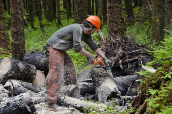 Erik Boraas, executive director of Trail Mix, cuts logs to be hauled off the trail.