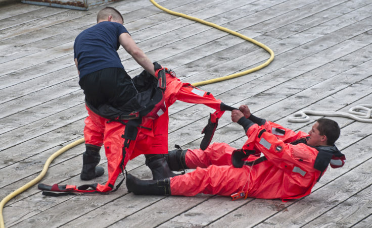 Teammates help each other remove the heavy survival suits following the swimming competition.