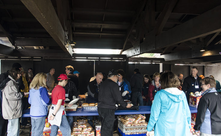 People line up for grilled salmon, hot dogs, chips and drinks.