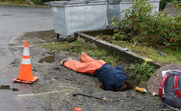 ADEC responder, Crystal Smith, checks manhole for potential pathways.