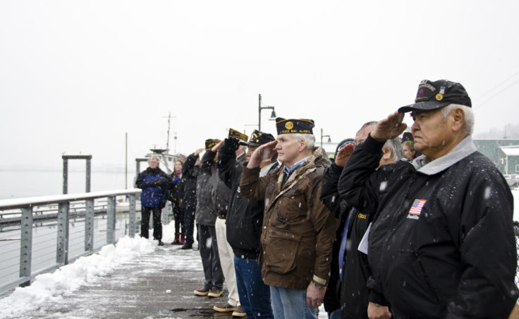 Veterans salute the flag during the playing of Taps.