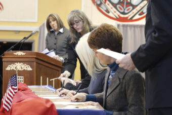 Alaska electors Kathleen Miller and Kristie Babcock sign Alaska's electoral votes while Election Coordinator Lauri Wilson takes an electoral ballot from elector Christopher Nelson at the 2012 Electoral College vote casting. (Photo by Annie Bartholomew/KTOO)