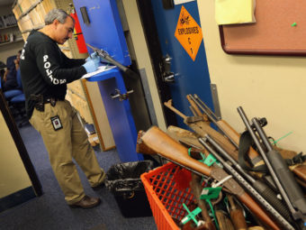 Detective Enrique Chavez logs weapons from a gun buyback in Miami. Arizona's new law requires municipalities to re-sell weapons recovered in such programs. Joe Raedle/Getty Images