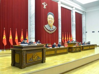 North Korea's KCNA news agency released this photo Monday, saying it shows leader Kim Jong Un (at left) speaking during a plenary meeting of the Central Committee of the DPRK in Pyongyang. Hanging above is the image of his father, former leader Kim Jong Il, who died in 2011. Xinhua /Landov