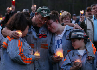 In this 2010 photo, coal miner Terry Cooper, left, embraces his wife Michelle, daughter Tera and son Justin, during a vigil to honor the coal miners that were killed in Montocal, West Virginia. Mark Wilson/Getty Images