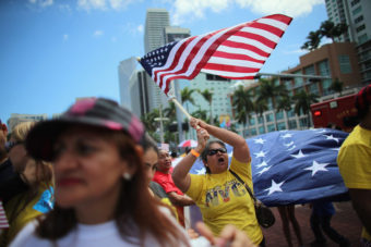 Maglena Gomez waves an American flag as she and others participate in a march that organizers said was an attempt to get the U.S. Congress to say yes to immigration reform on April 6, 2013 in Miami, Florida. Joe Raedle/Getty Images
