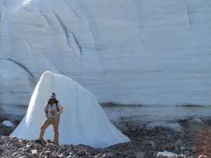 As the Teardrop Glacier on Ellesmere Island in the Canadian Arctic recedes, researchers have found a kind of evergreen plant called bryophytes coming out from beneath the ice. Here, a researcher stands next to part of the glacier for scale. Courtesy of Catherine La Farge