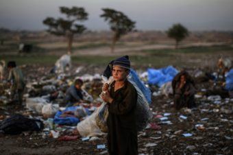 Afghan refugee children collect items of use from a pile of garbage on the outskirts of Islamabad, Pakistan. Muhammed Muheisen/AP