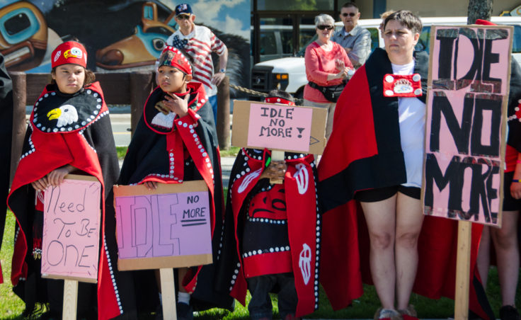 Dancers hold signs while watch a speech at the rally. (Photo by Heather Bryant/KTOO)