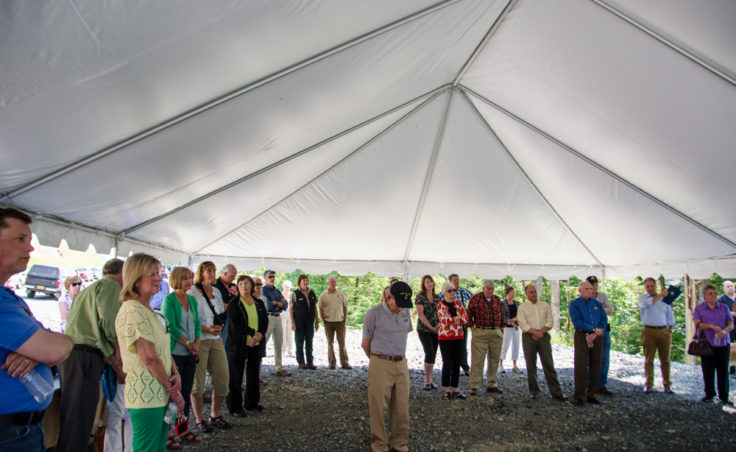 A crowd of approximately 50 people made the journey to the end of the road for the ribbon-cutting. Concerned about afternoon rain showers, DOT sent up a large tent for the speakers. It served as a magnet for large black flies.