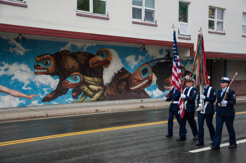 The color guard marches past City Hall