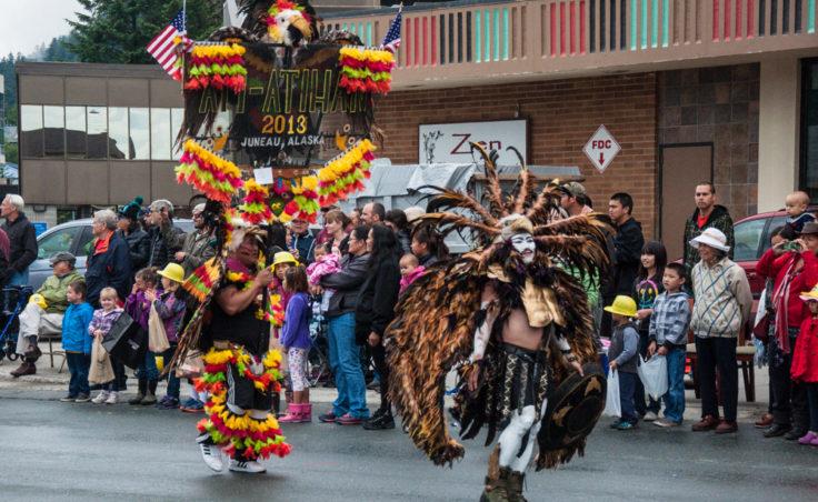 Costumed dancers make their way down Egan