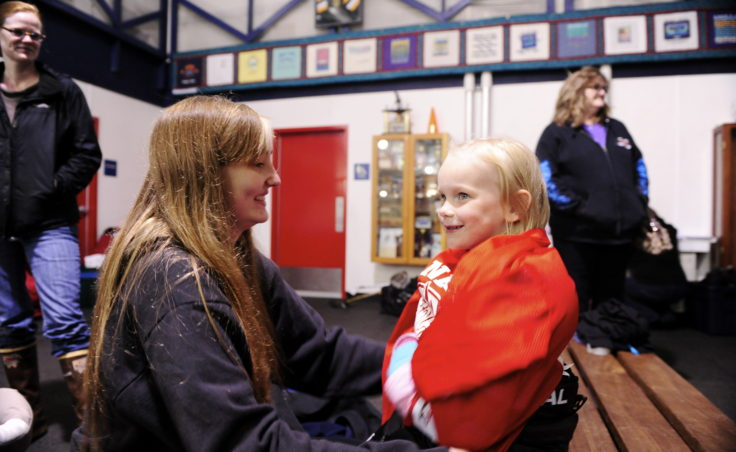 Myrica Wildes helps Lydia Heidemann find a jersey that fits before Lydia gets on the ice at JDIA's Learn to Play event Saturday.