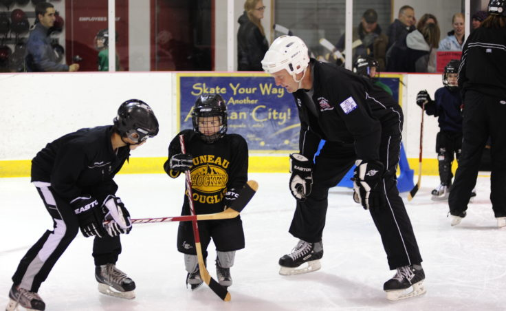 Greyson Liebelt (left) and Bill Wildes welcome a young player a few steps after he steps onto the ice at during JDIA's Learn to Play event Saturday at Treadwell Arena.