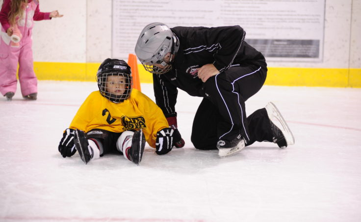 JDIA coach Jim deLaBruere helps Trevor Stephens during JDIA's Learn to Play event Saturday at Treadwell Ice Arena.