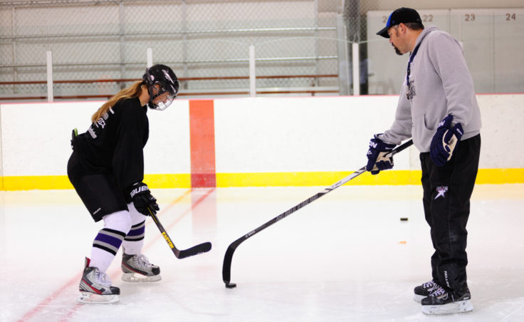 Bryan Smith works with Emma Kaelke during a shooting drill drawn up by Smith at the Rocky Mountain Hockey School.