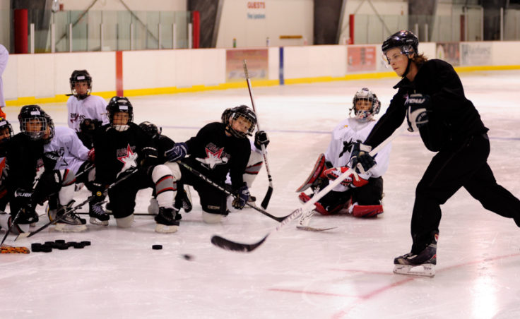 Logan Hulse demonstrates proper shooting technique while players attending the Rocky Mountain Hockey School watch in awe of his accuracy.