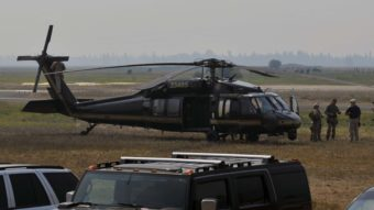 Authorities wait near a blackhawk helicopter at the Cascade Airport in Cascade, Idaho, on Saturday as they comb Idaho's Frank Church River of No Return Wilderness. Robby Milo/Associated Press