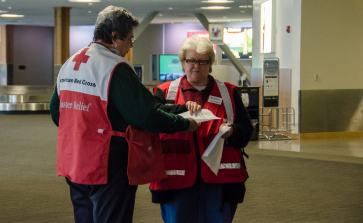 Red Cross volunteers wait inside the airport terminal to direct arriving family members to the waiting area.