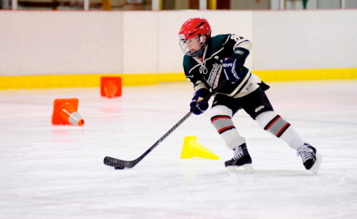 Gabe Miller weaves in and out of cones while advancing the puck during a drill at Treadwell Ice Arena.