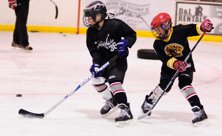 Finn Shibler evades Gage Cooney during a puck possession drill at Steve MacSwain's two-day hockey camp held at Treadwell Ice Arena.