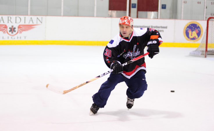 Steve MacSwain demonstrates a passing and shooting drill he wants a group of hockey players to attempt themselves.