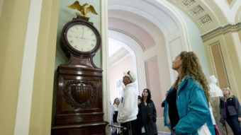 Still Right Twice A Day: Visitors look at the Ohio Clock outside the Senate chamber on Capitol Hill Sunday. The clock that has stood watch over the Senate for 196 years stopped running shortly after noon Wednesday. Employees who wind the clock weekly were furloughed in the federal shutdown. Jose Luis Magana/AP