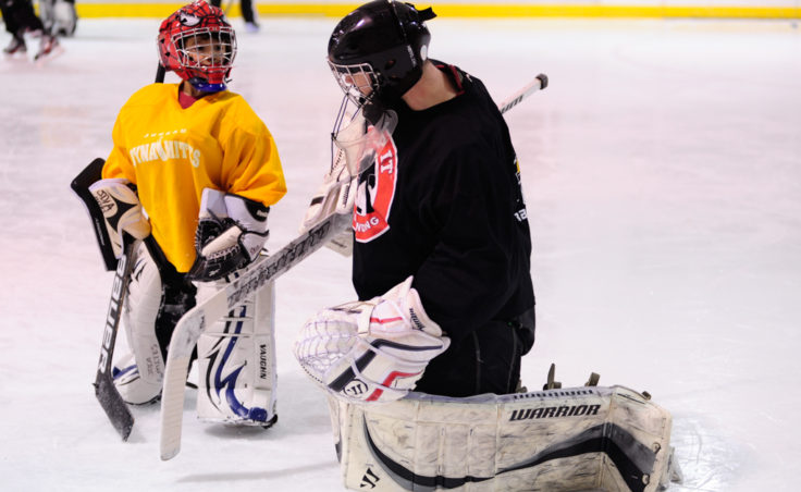 Neal Chapman, right, pulls double duty as a student and teacher as a group of goalies work on their game during a JDIA skills development camp.