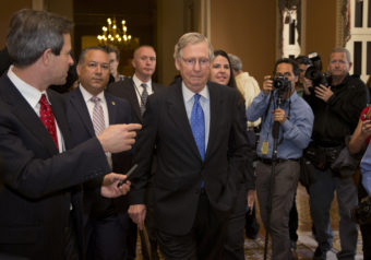 Senate Minority Leader Sen. Mitch McConnell, R-Ky., walks to the Senate floor after agreeing to the framework of a deal to avoid default and reopen the government, on Capitol Hill on Wednesday. Carolyn Kaster/AP