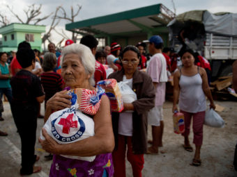 An elderly woman and others leave after getting some help from Red Cross volunteers Monday in Dagami, the Philippines, about 20 miles south of the city of Tacloban. Millions of people need assistance because their homes were destroyed by Typhoon Haiyan on Nov. 8. Odd Andersen /AFP/Getty Images