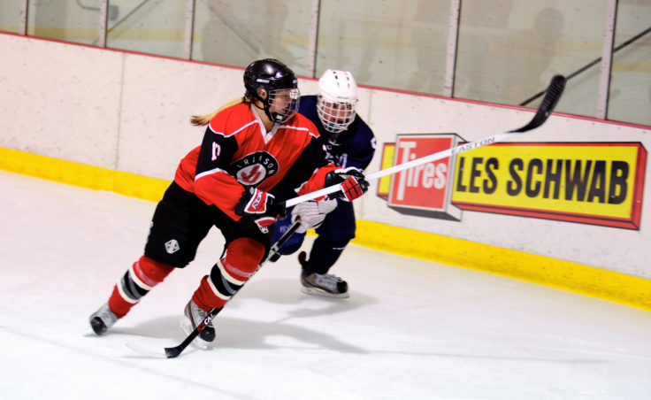 Defenseman Kathryn Noreen stays a step ahead of Nick Wrobel during the team's season opening series versus Soldotna.