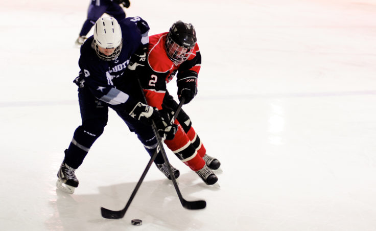 Juneau captain Grant Ainsworth battles Stephen Endsley for the puck in the team's season opener at Treadwell Ice Arena.