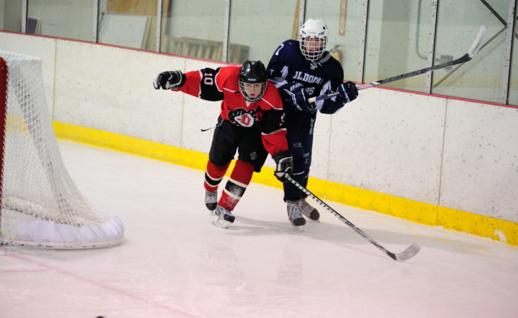 Juneau center Ethan Seid pokes the puck away from Levi Hensley during the team's season opening series versus Soldotna at Treadwell Ice Arena.