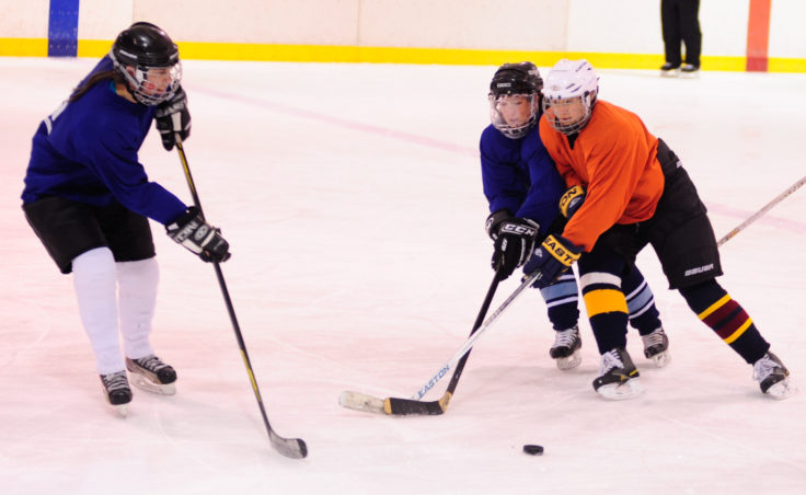 Angel Kwok (orange) leans into Carrie Bohan while trying to advance the puck and Bohan's teammate Kristine Eastman awaits during during the 10th Annual Jamboree women's hockey tournament at Treadwell Ice Arena.