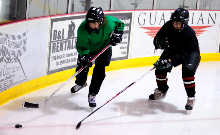 Katie Spielberger tracks down puckhandler Christine Woll during the 10th Annual Jamboree women's hockey tournament at Treadwell Ice Arena.