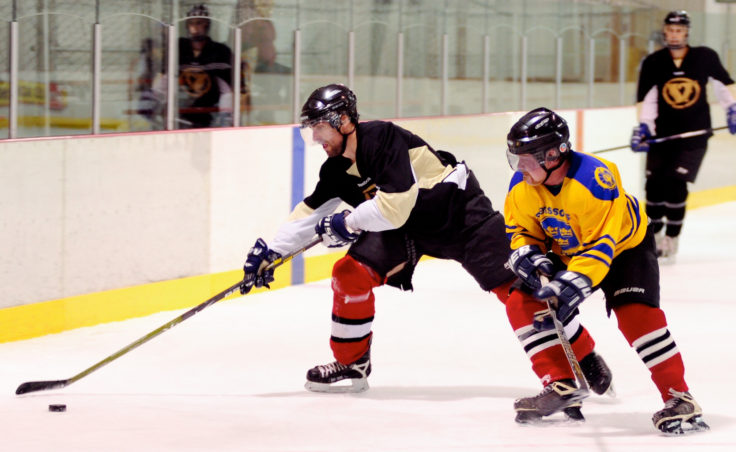 Svensson's Boatworks' Austin Osterhout leans into Viking player Taylor Horne during a first-round playoff Tier A playoff game.