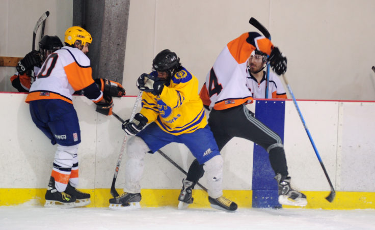 Island Pubs' Davin Savikko (left) and Carlton Foss squeeze Svensson Boatworks' Aaron Jacobs as all three battle for the puck along the boards in a Tier A title game.